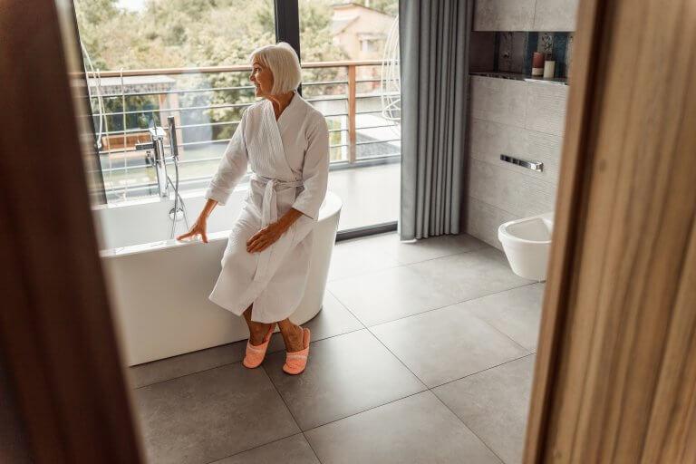 Joyful senior lady in bathrobe looking out of the window